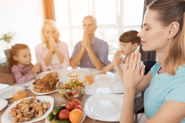 People at the table put their hands together and pray.