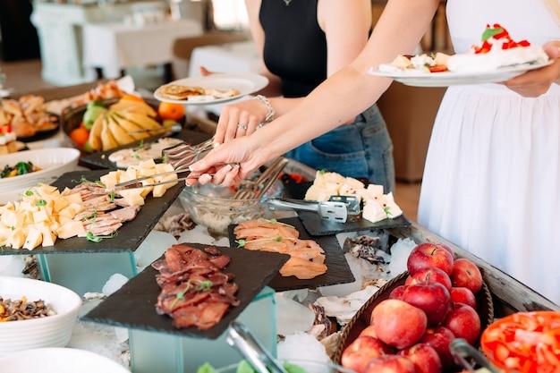 Люди едят шведский стол в ресторане отеля
