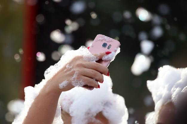 Люди фотографируют себя на мобильный телефон на мыльной дискотеке