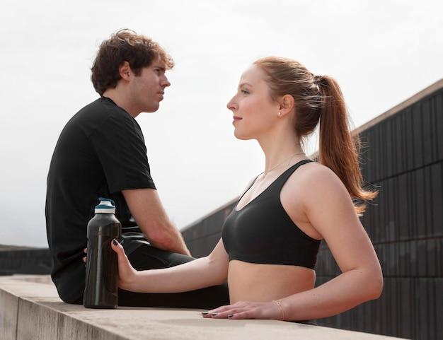 Люди, отдыхающие от занятий фитнесом на открытом воздухе