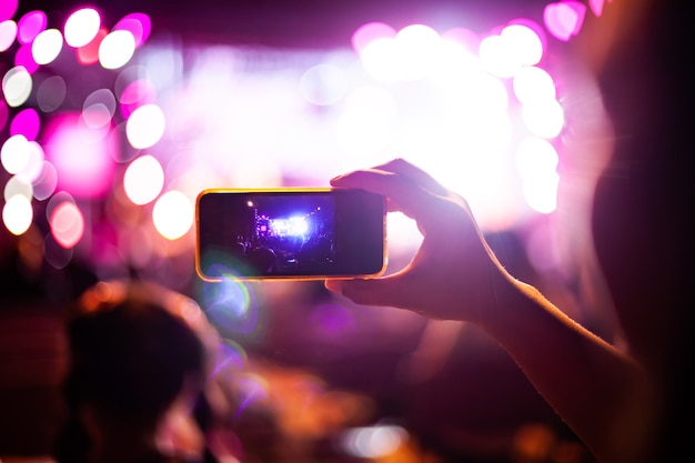People taking photographs with smart phone during live music concert and crowd