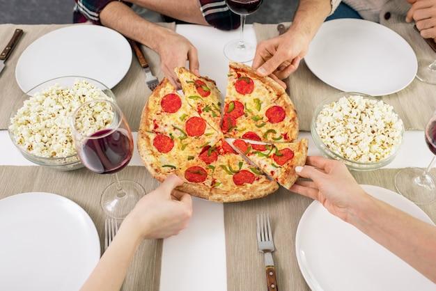 ピザのスライスを取る人々