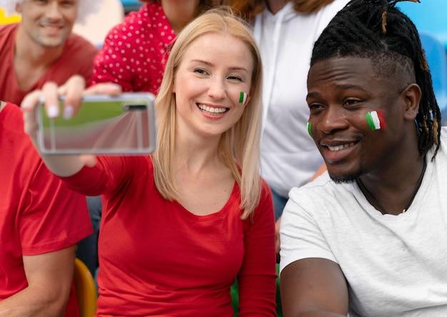Persone che si fanno un selfie a una partita di calcio