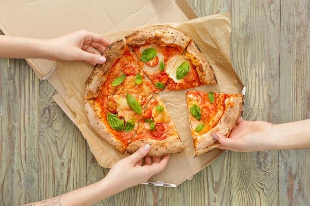 テーブルからおいしいピザマルゲリータのスライスを取る人々