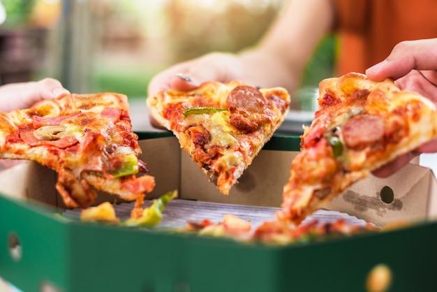 人々はピザのスライスを取る