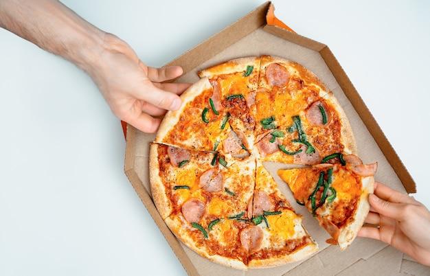 Люди берут кусочки вкусной пиццы пепперони на светлом фоне, вид сверху с копией пространства. баннер пиццы или баннер итальянской кухни. руки, делящие кусок пиццы из коробки для пиццы