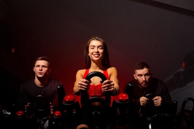 날씬한 몸매를 위해 기계 에어로빅으로 체중 감량을하는 사람들, 자전거에 앉아, 피트니스 체육관에서 집중 심장 운동