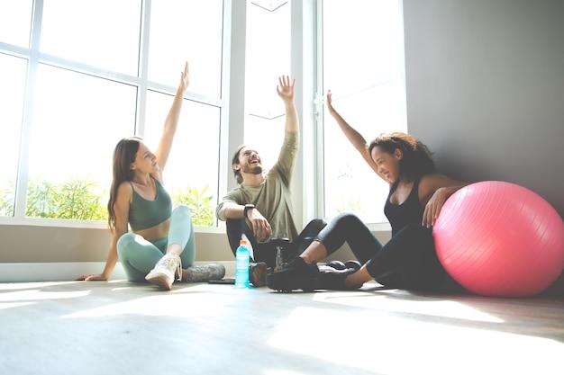 Люди разговаривают и смеются, счастливы вместе после тренировки в тренажерном зале. концепции здорового образа жизни и спорта.