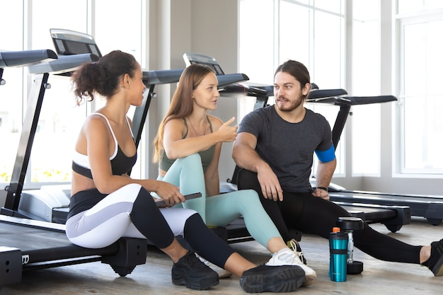 Люди разговаривают и смеются вместе после тренировки в тренажерном зале. концепция фитнеса и здорового образа жизни.