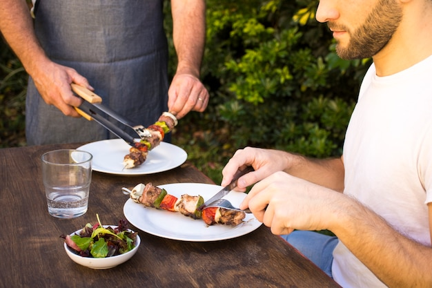 People tasting cooked barbecue in plates on table