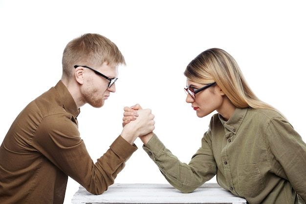 People, teamwork, cooperation and competition concept. side view of young female and bearded male colleagues both wearing glasses arm wrestling, staring at each other with confident determined looks
