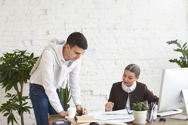 People, teamwork, cooperation and job concept. attractive young male architect standing at desk holding pencil while showing technical drawings to his middle aged female boss in modern office interior