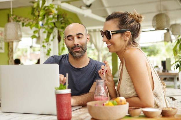 人、テクノロジー、コミュニケーション。カフェでラップトップコンピューターを使用して、新鮮な飲み物とテーブルに座っている大人のカップル。ノートに彼のガールフレンドに何かを示すハンサムな男。