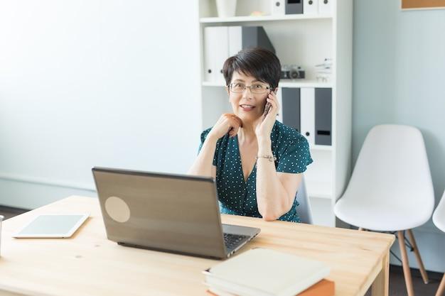 Люди, технологии и концепция коммуникации - женщина средних лет звонит на смартфон