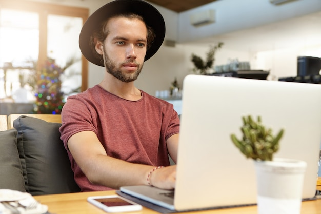 人、技術、コミュニケーションの概念。カフェで無料の高速インターネット接続を使用して、開いているラップトップの前に座ってリモートで作業しているスタイリッシュな帽子の深刻なひげを生やしたフリーランサー