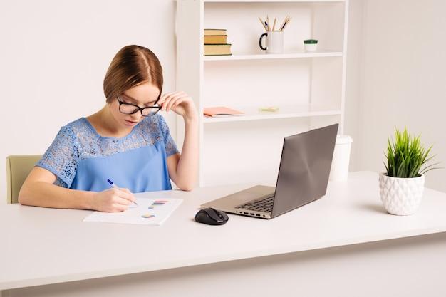 사람, 기술 및 교육 개념-집에서 노트북 컴퓨터와 책 테이블에 앉아 행복 미국 젊은 여자