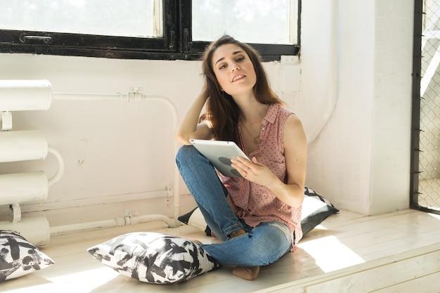 사람, 기술 및 인테리어 개념-태블릿 바닥에 앉아 행복 한 젊은 여자