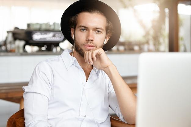 人、技術、レジャーのコンセプト。彼のラップトップコンピューターでオンライン音楽アプリを使用して、ひげのイヤホンで曲を聴くとファッショナブルな若い男