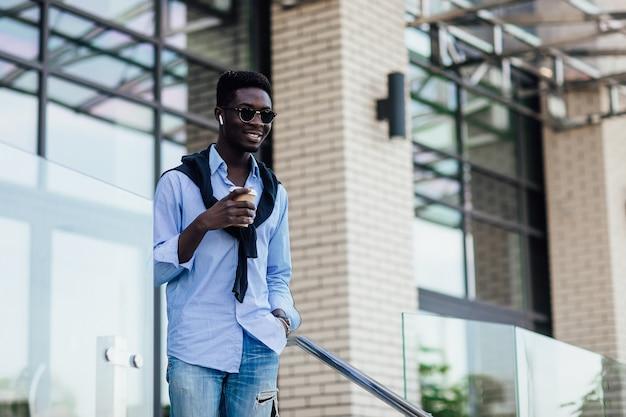 사람, 기술, 생활 방식 - 헤드폰과 스마트폰으로 도시에서 커피 한 잔과 함께 음악을 들으며 행복한 젊은이입니다.