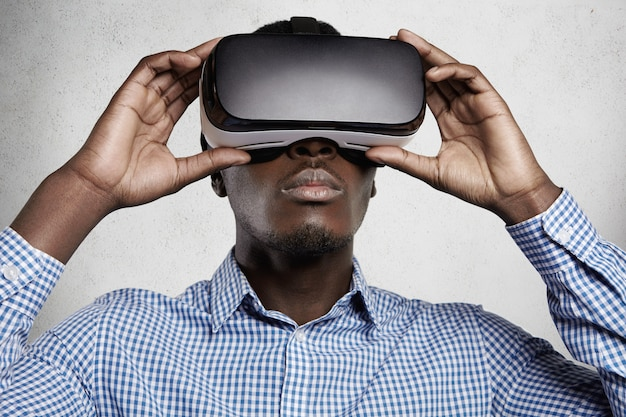People, technology, cyberspace and entertainment concept. african man dressed in checkered shirt using 3d headset, playing video games.