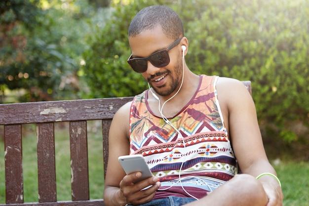 人、テクノロジー、レジャー、ライフスタイル-幸せな流行に敏感な学生が屋外でリラックスしながらスマートフォンを使用してインターネットをサーフィンします。一人でリラックスできるベンチに座っているヘッドフォンを着ている若いフリーランサー
