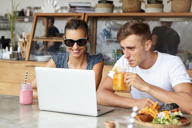People, technology and leisure concept. cute couple having fun