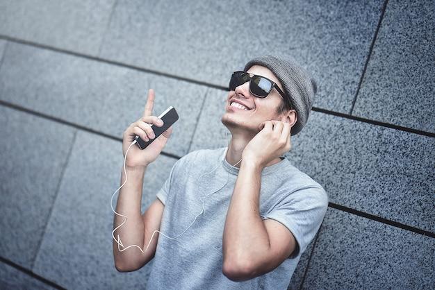 Люди, технологии, путешествия и туризм - мужчина с наушниками, смартфон на городской улице и слушает музыку на сером фоне стены
