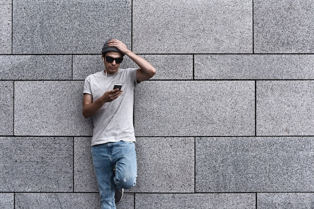 People, technology, travel and tourism  hipster man wearing hat, smartphone on city street and listening to music over gray wall background