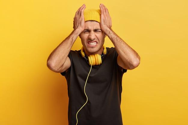 人、緊張、頭痛。不機嫌な男性モデルは、ストレスと絶望的な痛みと片頭痛に苦しんでいます