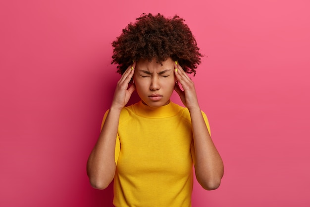 People, tiredness, medicine, symptom concept. unhappy distressed ethnic woman has high blood pressure, rubs temples to relieve headache, keeps eyes shut, has unbearable migraine, poses indoor