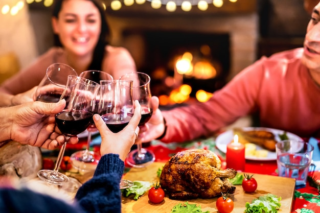 People toasting red wine having fun at christmas dinner reunion
