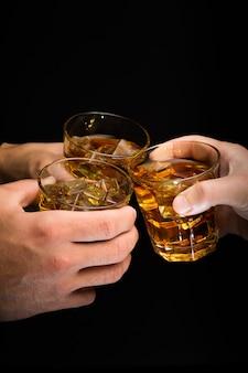 黒の背景に昔ながらのグラスで乾杯する人々