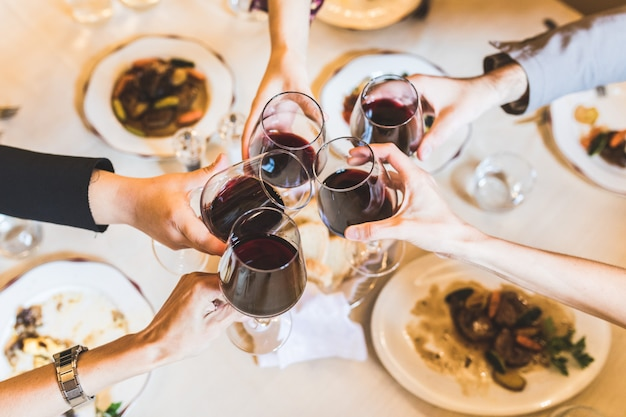 People toasting with red wine at restaurant