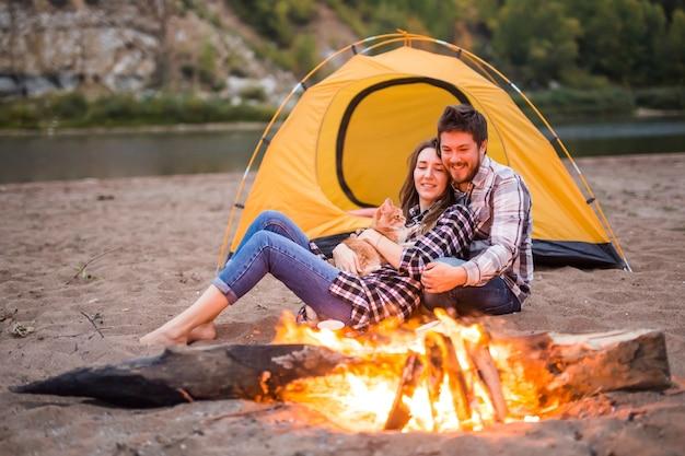 사람, 관광 및 자연 개념-남자는 불 근처에 앉아 여자를 포용.