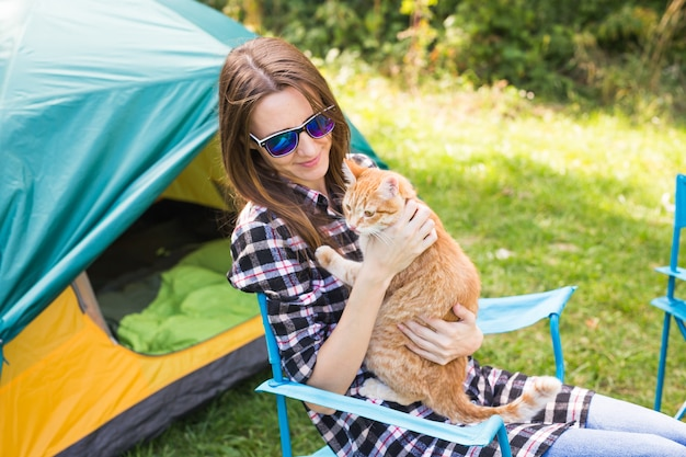People, tourism and nature concept - woman in sunglasses stroking a cat sitting near the tent.