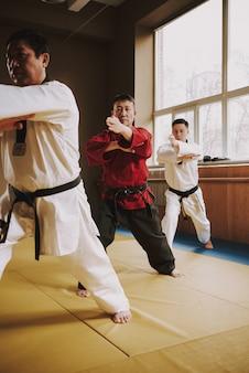 Люди тренируют удары в боевой комнате по каратэ.