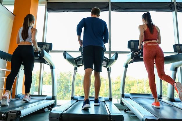 Люди тренируются на беговых дорожках в тренажерном зале