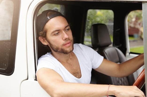 人、交通、レジャー。若いひげを生やした学生彼の白いジープレザーキャビンの内側に座って、道路で彼の前を見てスタイリッシュなスナップバックを着て