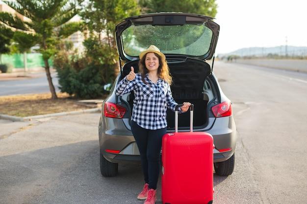 사람, 교통 및 여행 개념입니다. 쾌활한 여자가 그녀의 차 근처에 서서 트렁크를 닫고 있습니다.