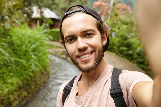 People, travel and adventure concept. attractive young bearded adventurer wearing backpack and cap taking selfie