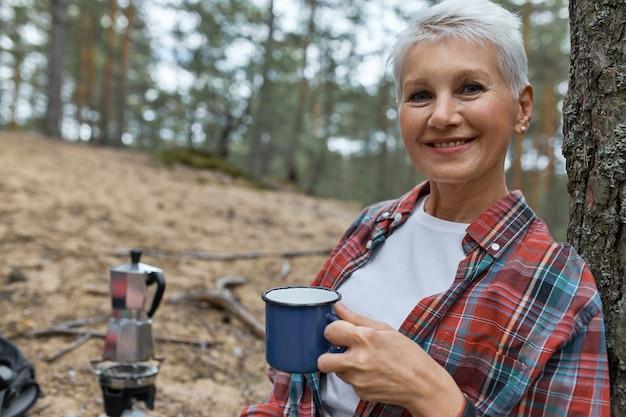 人、旅行、ハイキング、休暇。カップを持って屋外でポーズをとる、野生の自然の中でお茶を飲む、松林のキャンプ場で休む、平和な雰囲気を楽しむ楽しい中年の白人女性