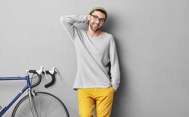 人、旅行、レジャー、ライフスタイルのコンセプトです。彼の仲間が一緒に乗って大都市や町を探索するのを待っている間自転車の近くに立っている流行の服で笑顔の流行に敏感な若者
