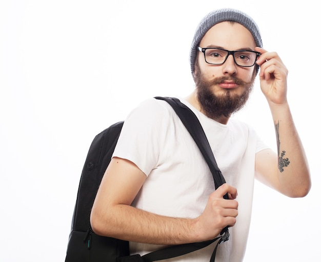 人、旅行、観光、教育の概念。白のバックパックで、帽子をかぶって眼鏡をかけた幸せな若いひげを生やした男