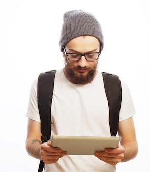 人、旅行、観光、技術の概念-白い背景の上のバックパックとタブレットと眼鏡で幸せな若いひげを生やした男。流行に敏感なスタイル。ポジティブな感情。
