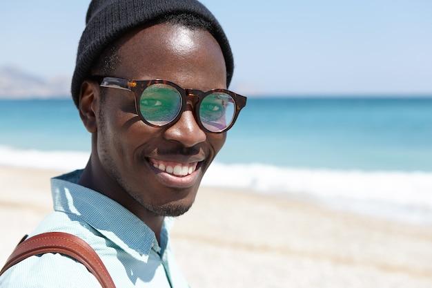 人、旅行、休暇、ライフスタイル、観光、幸福の概念。ビーチで週末の朝を過ごすハンサムな屈託のないリラックスした男性
