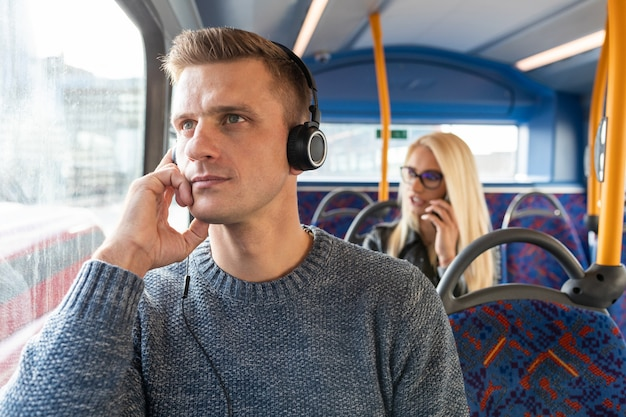 People traveling by bus in london and keeping social distance - man and woman commuting on empty bus in the city and keeping safe distance