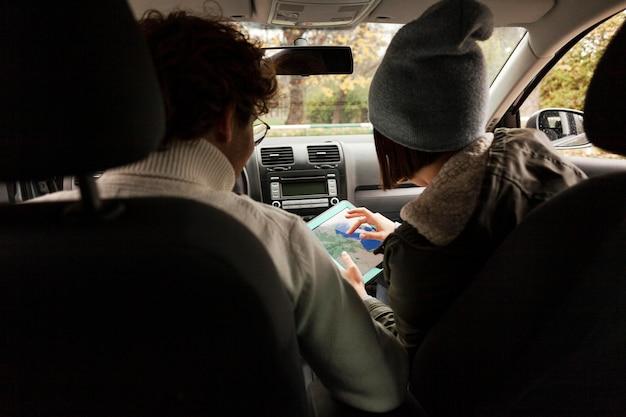 一緒に車で旅行し、新しい目的地をチェックする人々