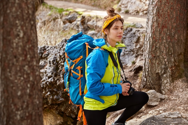 People, trekking, challenge, adventure concept. healthy female hiker treks to mountain peak through forest, makes photos of landscapes with camera
