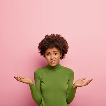 People and uncertainty concept. displeased hesitant female model spreads palms with doubt, looks confusingly , wears green sweater, poses against pink wall, copy space upwards