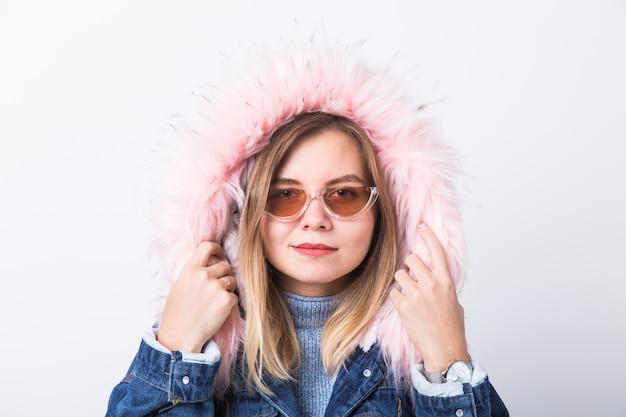 人々、都会的なスタイルとファッションのコンセプト-白い壁にジーンズのコートを着ているスタイリッシュなヒップスターの女の子。